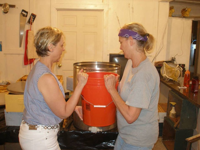 Transferring honey from the straining bucket into the holding tank.  This is where the honey will sit for about 48 hours to allow air bubbles to rise to the top in preparation for bottling.